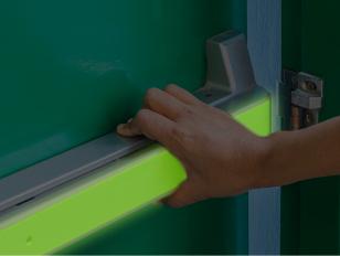 Glow in the dark adhesive material for door handles